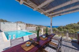 Обеденная зона. Греция, Агия Пелагия : Прекрасная вилла с бассейном, зеленой лужайкой, барбекю и видом на море, 3 спальни, 3 ванные комнаты, парковка, Wi-Fi