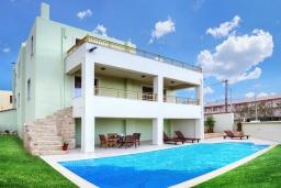 Фасад дома. Греция, Скалета : Современная и элегантная вилла с 5-ю спальнями, с бассейном, зелёным двориком, тенистой террасой с патио, барбекю, расположена всего в 70 метрах от пляжа