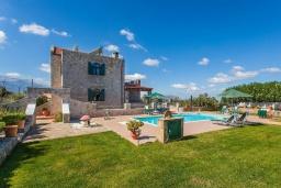 Фасад дома. Греция, Георгиуполис : Впечатляющая вилла с 3 спальнями, с большим бассейном, зелёным садом,  патио и барбекю, расположена в деревне Litsarda