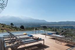 Зона отдыха у бассейна. Греция, Каливес : Роскошная современная вилла с панорамным видом на море, с 4 спальнями, с большим бассейном, зелёной лужайкой и барбекю