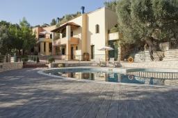 Фасад дома. Греция, Георгиуполис : Каменный дом в комплексе с бассейном, с 2 спальнями, террасой и потрясающим видом на горы, море и окрестности