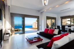 Гостиная. Греция, Элунда : Роскошная современная вилла с панорамным видом на море и окрестности, с 3 спальнями, с большим бассейном, тренажерным залом, джакузи, барбекю