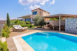 Фасад дома. Греция, Айя Пелагия : Роскошная вилла с бассейном, зеленым двориком с барбекю и видом на море, 5 спален, 3 ванные комнаты, парковка, Wi-Fi