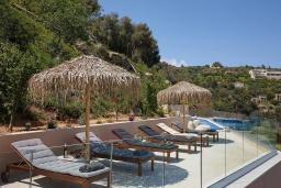 Зона отдыха у бассейна. Греция, Ираклион : Роскошная вилла с большим бассейном и видом на море, 2 гостиные, 4 спальни, 3 ванные комнаты, барбекю, парковка, Wi-Fi