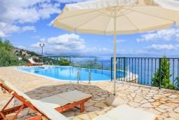 Зона отдыха у бассейна. Греция, Нисаки : Прекрасная вилла с бассейном и видом на море, 2 спальни, 2 ванные комнаты, барбекю, парковка, Wi-Fi