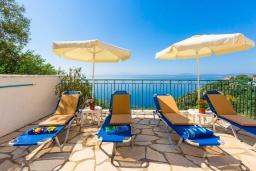 Зона отдыха у бассейна. Греция, Нисаки : Прекрасная вилла с бассейном, двориком с барбекю и видом на море, 3 спальни, 3 ванные комнаты, парковка, Wi-Fi