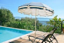 Зона отдыха у бассейна. Греция, Кроузери : Прекрасная вилла в 80 метах от пляжа с бассейном, двориком с барбекю и видом на море, 3 спальни, 3 ванные комнаты, парковка, Wi-Fi