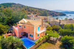 Фасад дома. Греция, Айос Стефанос : Уютная вилла 150 метрах от пляжа, с бассейном, двориком с барбекю и видом на море, 4 спальни, 3 ванные комнаты, парковка, Wi-Fi