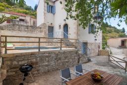 Фасад дома. Греция, Георгиуполис : Каменный дом с 2 спальнями, бассейном и приватным двориком с барбекю и тенистым патио
