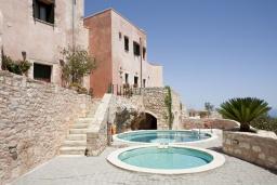 Фасад дома. Греция, Георгиуполис : Комплекс из 4 домов с видом на море и горы, с общим бассейном, приватной террасой, патио и барбекю