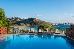 Бассейн. Греция, Айос Николас : Прекрасная вилла в классическом средиземноморском стиле с потрясающим видом на море, с 4 спальнями, с бассейном, тенистой террасой с lounge-зоной, расположена на побережье Aghios Nikolaos