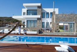 Фасад дома. Греция, Элунда : Роскошная современная вилла с панорамным видом на море, с 4 спальнями, с бассейном, солнечной террасой, патио, барбекю и тренажерным залом