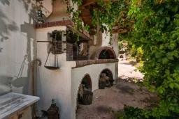 Территория. Греция, Скалета : Уютная вилла с 5 спальнями, бассейном, зелёным двориком с беседкой с патио и каменным барбекю, расположена в деревне Prinos