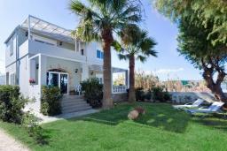 Фасад дома. Греция, Киссамос Кастели : Очаровательная уютная вилла с потрясающим видом на Эгейское море, с 4 спальнями, с красивым зелёным садом с шезлонгами, патио и барбекю, расположена в 10 метрах от пляжа Drapanias